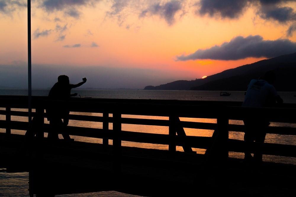 Casal aproveita pôr do sol no trapiche de Morrinhos, em Bombinhas SC. Fonte: Rodrigo Dalri.